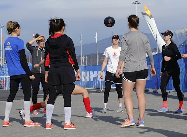 Members of the Canadian women's ice hockey team warm up outside before their game against the United States during the 2014 Winter Olympics women's ice hockey tournament at Shayba Arena, Wednesday, Feb. 12, 2014, in Sochi, Russia. (AP Photo/J. David Ake)