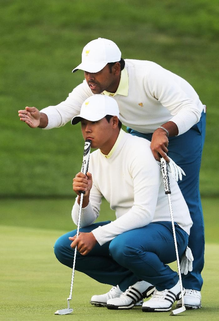 Anirban Lahiri and Kim Si Woo of the International Team line up a putt during Saturday four-ball matches of the Presidents Cup, at Liberty National Golf Club in Jersey City, New Jersey, on September 30, 2017 (AFP Photo/SAM GREENWOOD)