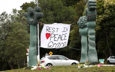 Tributes to Grace Millane are left at the roundabout in Titirangi, at the start of Scenic Drive in Auckland - Credit: Getty