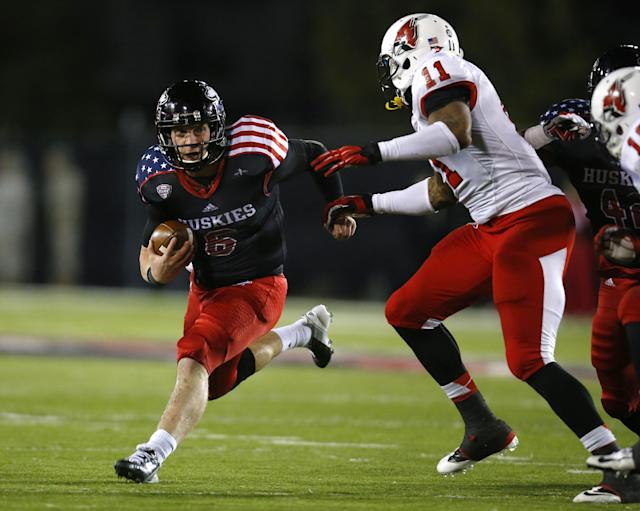 Northern Illinois quarterback Jordan Lynch (6) tries to avoid Ball State defensive end Jonathan Newsome (11) during the first half of an NCAA college football game Wednesday, Nov. 13, 2013, in DeKalb, Ill. (AP Photo/Jeff Haynes)
