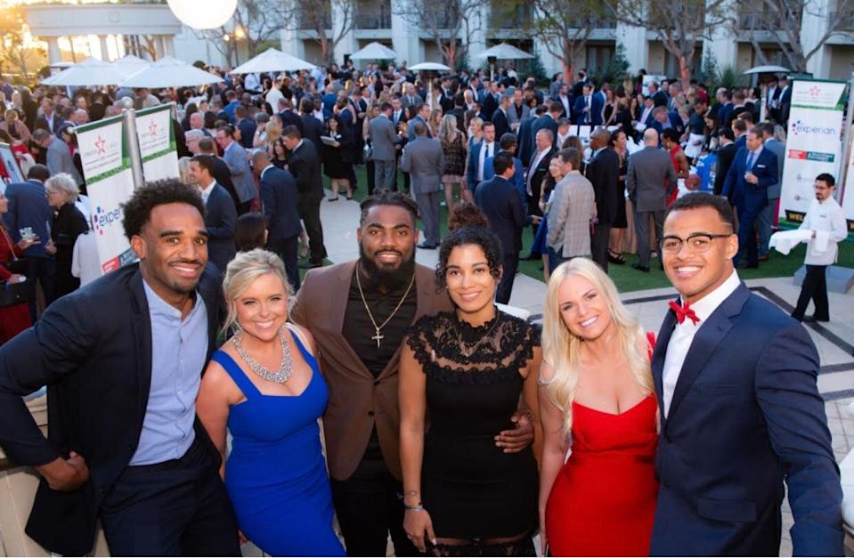 Savannah Foster (L), pictured with clients Landon Collins (M) of the Washington Redskins and Noah Fant (R) of the Denver Broncos at a company charity event, is an agent at Athletes First.