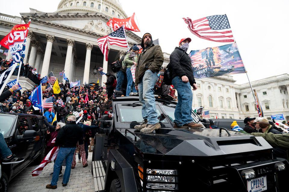 Trump supporters stand on U.S. Capitol Police armored vehicles as others take over the steps of the Capitol...