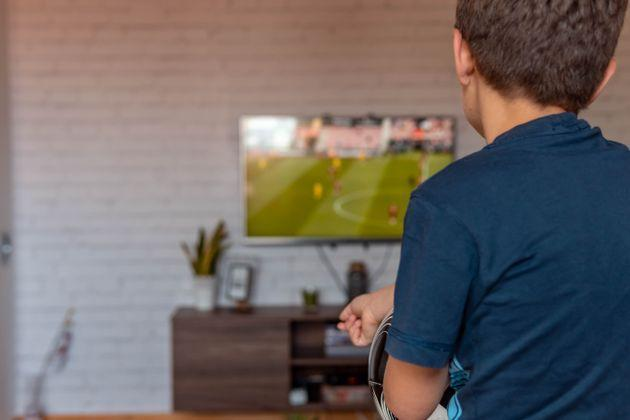 Rear view of boy watching TV at home. Boy watching soccer or football game on tv. (Photo: Bojan Vlahovic via Getty Images)