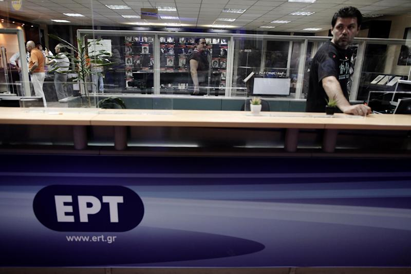 An employee looks on at the information desk of Greek state television ERT headquarters in Athens, on Tuesday, June 11, 2013. Greece is to close down all its state-run TV and radio stations with the loss of some 2,500 jobs as part of its cost-cutting drive demanded by the bailed-out country's international creditors. (AP Photo/Petros Giannakouris)