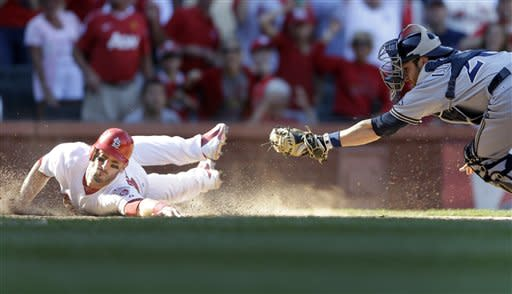 St. Louis Cardinals' Matt Carpenter, left, scores the game-winning run as Milwaukee Brewers catcher Jonathan Lucroy fails at the tag during the 10th inning of a baseball game, Sunday, Sept. 9, 2012, in St. Louis. The Cardinals won 5-4. (AP Photo/Jeff Roberson)