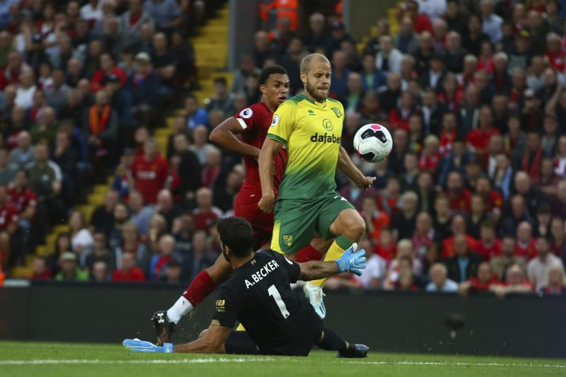 Liverpool's goalkeeper Alisson Becker, bottom, makes a save as Norwich City's Teemu Pukki tries to keep the ball during the English Premier League soccer match between Liverpool and Norwich City at Anfield in Liverpool, England, Friday, Aug. 9, 2019. (AP Photo/Dave Thompson)