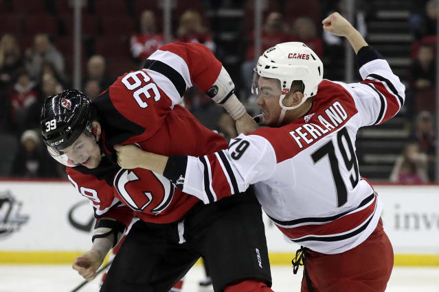 New Jersey Devils right wing Kurtis Gabriel (39) and Carolina Hurricanes left wing Micheal Ferland (79) fight during the first period of an NHL hockey game, Sunday, Feb. 10, 2019, in Newark, N.J. (AP Photo/Julio Cortez)