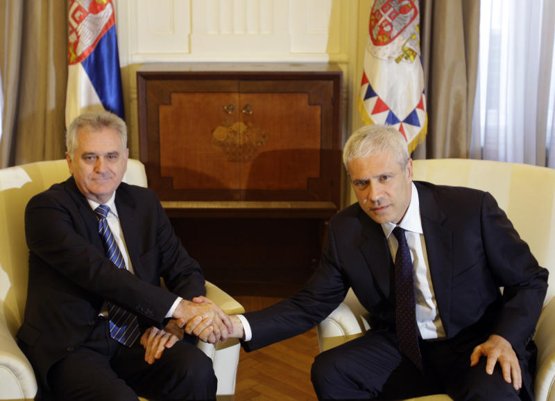 Newly elected Serbian President Tomislav Nikolic, left, shakes hands with former president Boris Tadic during meeting in the Serbian presidency building, in Belgrade, Serbia, Monday, May 28, 2012. Pro-EU Tadic, who is poised to become the new prime minister after losing the presidential vote, is launching coalition talks for the formation of the next government. (AP Photo/Darko Vojinovic)