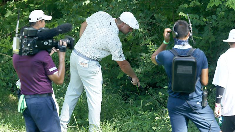 Pictured here, Bryson DeChambeau looks for his ball in the second round of the Memorial.