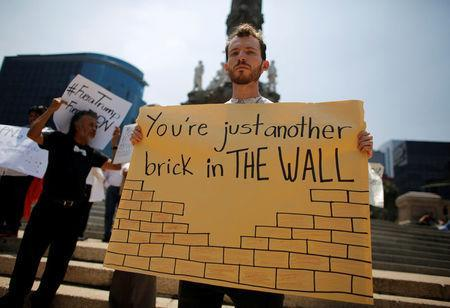A demonstrator holds a placard during a protest against the visit of U.S. Republican presidential candidate Donald Trump, at the Angel of Independence monument in Mexico City, Mexico, August 31, 2016. REUTERS/Tomas Bravo