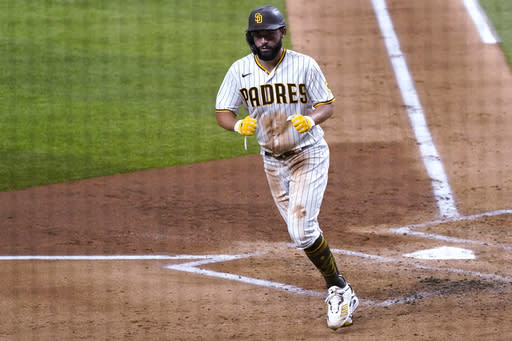 San Diego Padres' Eric Hosmer scores on a bases-loaded walk to Jake Cronenworth during the second inning in Game 3 of a baseball National League Division Series Thursday, Oct. 8, 2020, in Arlington, Texas. (AP Photo/Tony Gutierrez)