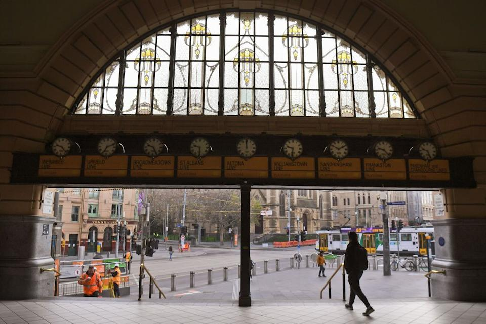 A commuter exits the usually bustling Flinders Street station in Melbourne on July 10, 2020, as the city re-enters a lockdown after a fresh outbreak of the COVID-19 coronavirus. - Australia will slash the number of returning citizens allowed into the country by half as it struggles to contain an outbreak of coronavirus in its second-largest city, officials announced on July 10. (Photo by William WEST / AFP) (Photo by WILLIAM WEST/AFP via Getty Images)