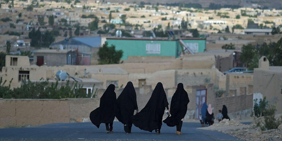 Photo credit: Women walk through a road in Ghazni in June 2021 - Getty Images