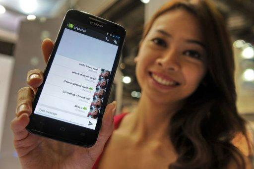 A model holds a mobile phone displaying a stream of text messages on its screen in Singapore. Text messaging, the humble telecoms service that turned into a global phenomenon, is under threat from free smartphone services and operators need to find alternative revenue streams, analysts say