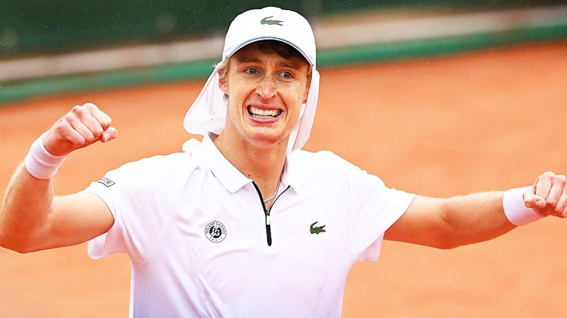 Marc Polmans fist-pumps and celebrates after winning match point at the French Open.