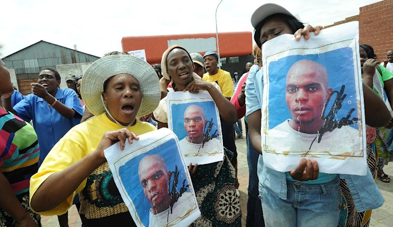 (FILES) -- This file photo taken on March 8, 2013 in Benoni shows protestors holding portraits of Mozambican taxi driver Mido Macia outside the Benoni court where police officers were charged with murdering him on February 26, 2013 in Daveyton, east of Johannesburg. Eight South African policeman were on August 25, 2015 found guilty of murdering a Mozambican man who died after being dragged behind a moving police van two years ago. The 27-year-old taxi driver died in police custody after being arrested for parking his car on the wrong side of the road. AFP PHOTO / ALEXANDER JOE (AFP Photo/Alexander Joe)