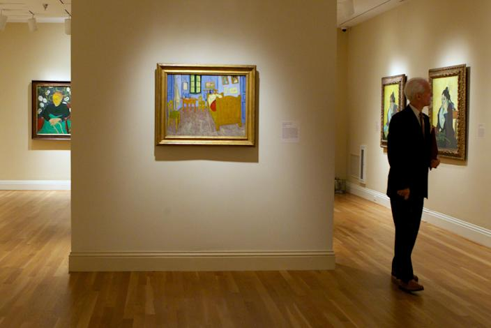 In this Oct. 8, 2013 photo, a member of the media walks through an exhibit of Vincent van Gogh on display at The Phillips Collection in Washington. In the midst of the shutdown of federally funded museums, the private Phillips Collection is launching the first major exhibition of Vincent van Gogh's artwork in Washington in 15 years. (AP Photo/Molly Riley)