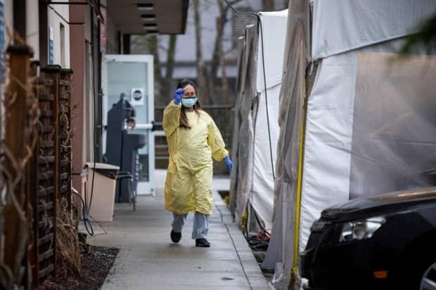 A health-care worker is seen at a COVID-19 testing centre at Ridge Meadows Hospital in Maple Ridge, B.C., earlier this month after a case of a coronavirus variant was detected at a nearby secondary school.