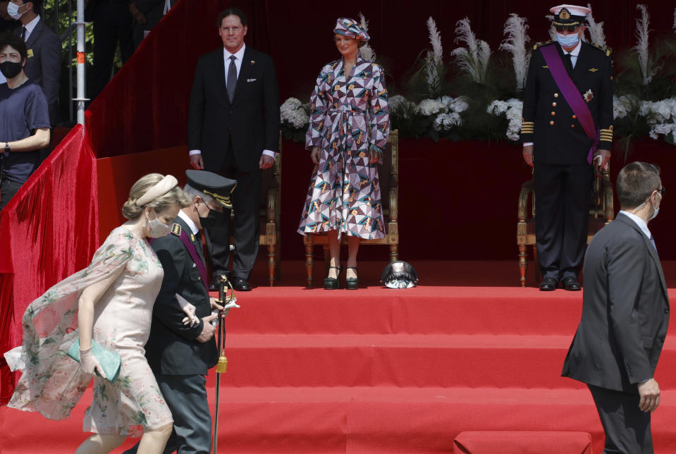Belgium's Princess Delphine, center rear and her husband James O'Hare, left rear, watch as Belgium's Queen Mathilde, left, and Belgium's King Philippe, second left, walk by after the National Day Parade in front of the Royal Palace in Brussels, Wednesday, July 21, 2021. Belgium celebrates its National Day on Wednesday in a scaled down version due to coronavirus, COVID-19 measures. (AP Photo/Olivier Matthys)