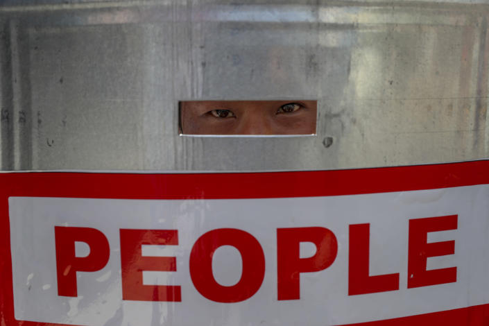 An anti-coup protester watch through a shield after police blocked their march in Mandalay, Myanmar, Wednesday, Feb. 24, 2021. Protesters against the military's seizure of power in Myanmar were back on the streets of cities and towns on Wednesday, days after a general strike shuttered shops and brought huge numbers out to demonstrate. (AP Photo)