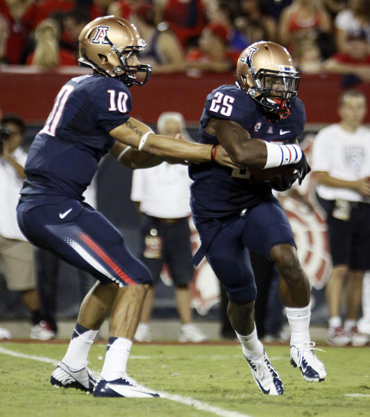 Arizona quarterback Matt Scott (10) hands off the ball to Ka'Deem Carey (25) during the first half against Oregon State in an NCAA college football game at Arizona Stadium in Tucson, Ariz., Saturday, Sept. 29, 2012. (AP Photo/Wily Low)