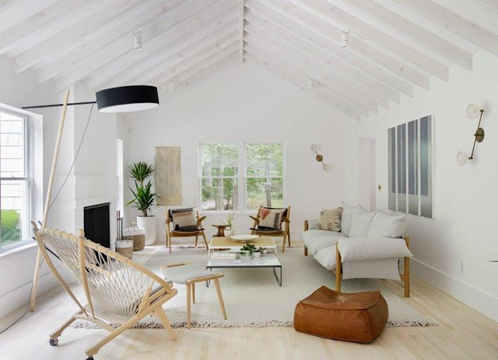 A spacious, white living room accented by lots of beachy Hamptons style decor pieces.