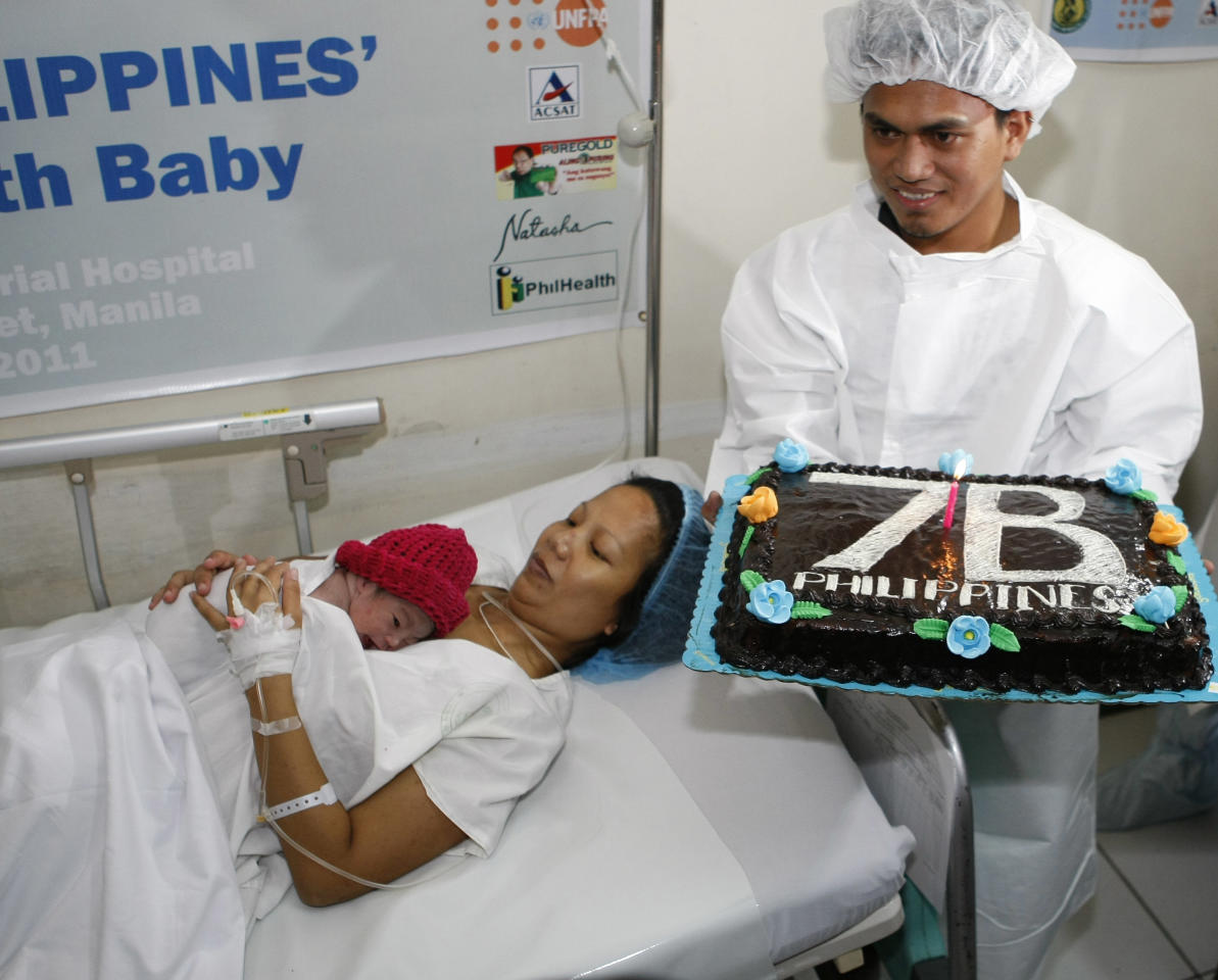 Danica Camacho is cuddled by her mother Camille as her father Florante Galura holds a cake shortly after she was born at the Government's Fabella Hospital Monday Oct.31, 2011 in Manila, Philippines. The Philippines, ranked 12th as the most populated country in the world, joins the rest of the world as it welcomes its symbolic 7 billionth baby in simple ceremony in Manila. (AP Photo/Bullit Marquez)