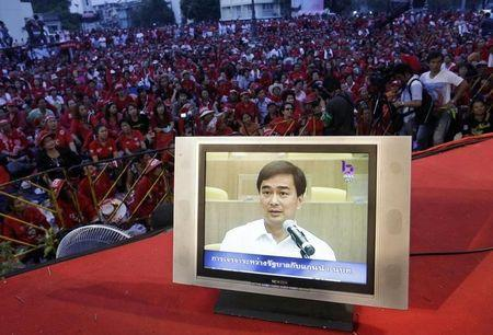 Footage of Thailand's Prime Minister Abhisit Vejjajiva negotiating with leaders of an anti-government demonstration is seen on the television at the demonstration in Bangkok March 29, 2010. REUTERS/Sukree Sukplang