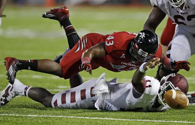 Temple quarterback P.J. Walker (11) fumbles the ball as he is tackled by Cincinnati linebacker Nick Temple (43) in the second half of an NCAA college football game, Friday, Oct. 11, 2013, in Cincinnati. Cincinnati recovered the fumble. (AP Photo/Al Behrman)