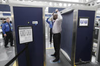 FILE - In this March 15, 2010 file photo, a volunteer passes through the first full body scanner installed at O'Hare International Airport in Chicago. The technology produces a cartoon-like outline rather than naked images of passengers by using X-rays. (AP Photo/M. Spencer Green, File)
