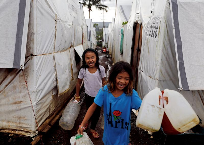 Girls carry water containers to be filled at an evacuation camp for families displaced by the Marawi siege, in Marawi City, Lanao del Sur province, Philippines. (Photo: Eloisa Lopez/Reuters)