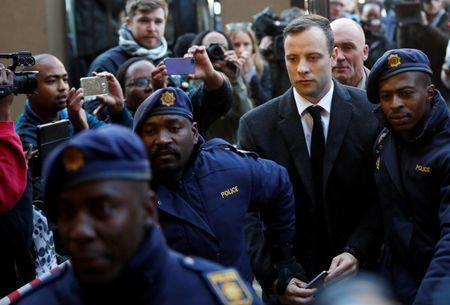 FILE PHOTO Paralympic gold medalist Oscar Pistorius is escorted by police officers as he arrives for his sentencing for the 2013 murder of his girlfriend Reeva Steenkamp, at Pretoria High Court, South Africa July 6, 2016. REUTERS/Siphiwe Sibeko/File Photo
