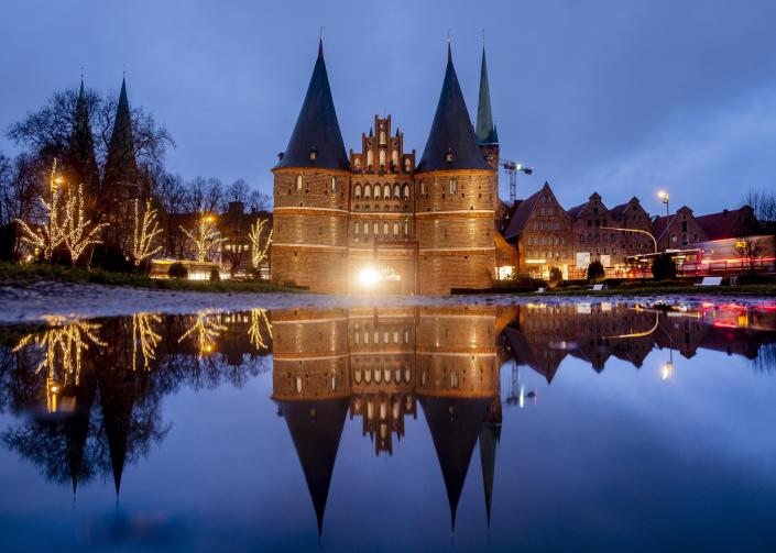 The medieval Holstentor is reflected in water in Luebeck, Germany, Monday, Jan. 4, 2021. The German government will decide about further restrictions to avoid the outspread of coronavirus on Tuesday. (AP Photo/Michael Probst)
