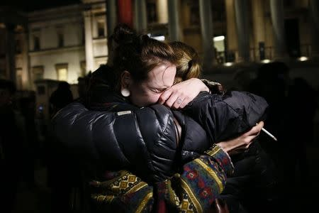 A woman cries during a vigil to pay tribute to the victims of a shooting by gunmen at the offices of weekly satirical magazine Charlie Hebdo in Paris, at Trafalgar Square in London January 7, 2015. REUTERS/Stefan Wermuth