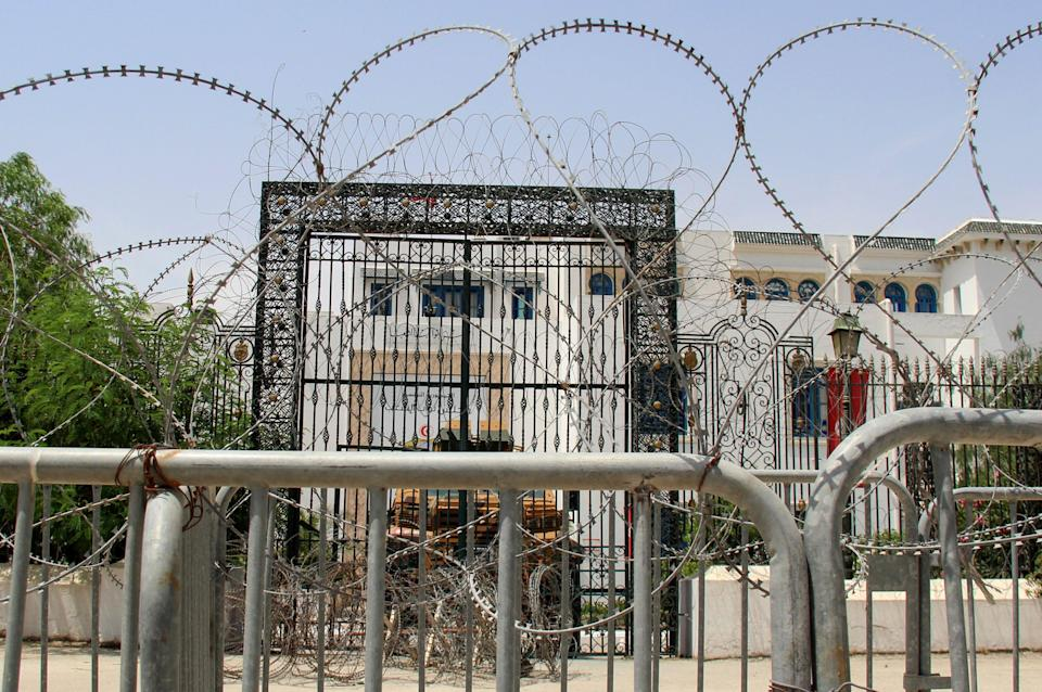 Barbed wire and a military armored personnel carrier block a side entrance of the Tunisian parliament (AP)