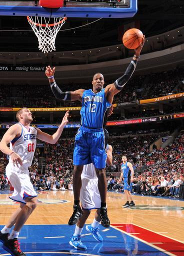 PHILADELPHIA, PA - APRIL 7: Dwight Howard #12 of the Orlando Magic grabs a rebound over Spencer Hawes #00 of the Philadelphia 76ers on April 7, 2012 at the Wells Fargo Center in Philadelphia, Pennsylvania. (Photo by Jesse D. Garrabrant/NBAE via Getty Images)