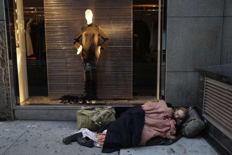 FILE - In this Wednesday, Nov. 20, 2013, file photo, a destitute man sleeps on the sidewalk under a holiday window at Blanc de Chine, in New York. A Gallup poll found two-thirds of Americans are dissatisfied with the nation's distribution of wealth. (AP Photo/Mark Lennihan, File)