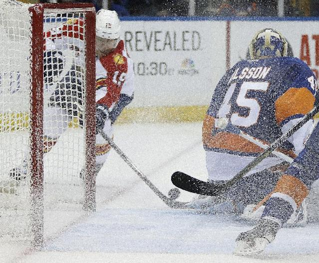 Florida Panthers right wing Scottie Upshall (19) maneuvers the puck behind New York Islanders goalie Anders Nilsson (45) ,of Sweden, during the third period of an NHL hockey game at Nassau Coliseum in Uniondale, N.Y., Sunday, March 2, 2014. Upshall had two goals as the Panthers defeated the Islanders 5-3. (AP Photo/Kathy Willens)