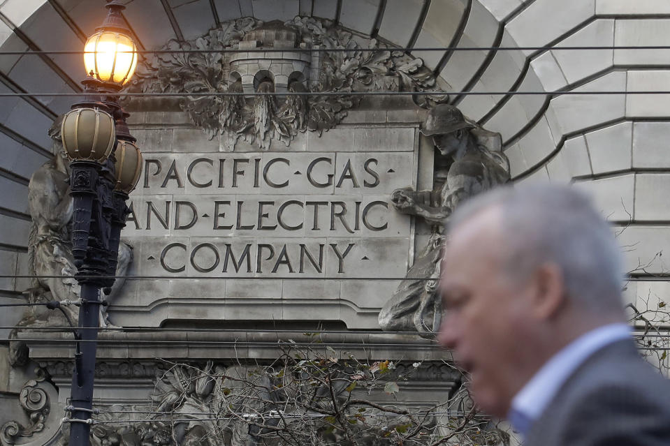 FILE - In this Dec. 16, 2019, file photo, a man walks by a Pacific Gas and Electric sign on a PG&E building in San Francisco. A federal judge overseeing Pacific Gas & Electric's criminal probation is considering requiring the utility to be more aggressive about turning off its electricity lines. The plan outlined Tuesday, March 23, 2021, would add more power shut-offs near tall trees and would at least double the number of power outages in six Northern California counties. (AP Photo/Jeff Chiu, File)