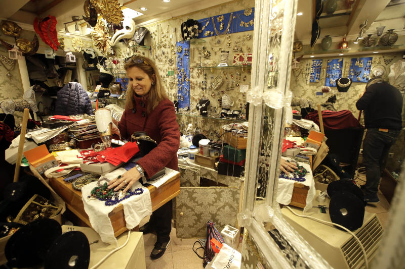 Sabrina Laggia uses a hair dryer to dry stone jewelry made by her husband, Alfredo, in their workshop near St. Mark's Square, Venice, Saturday, Nov. 16, 2019. Sabrina and Alfredo are recovering from Tuesday night's record flood and preparing to face dreading forecasts of a 1.6 meters (5.2 foot) tide forecast for next Sunday. High tidal waters returned to Venice on Saturday, four days after the city experienced its worst flooding in 50 years. AP Photo/Luca Bruno)