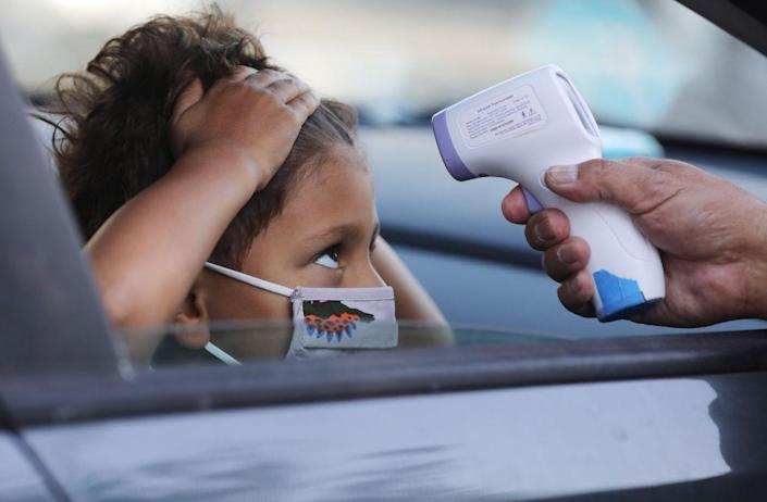 A student receives a temperature check before leaving the car to enter STAR Eco Station Tutoring & Enrichment Center on September 2, 2020 in Culver City, California