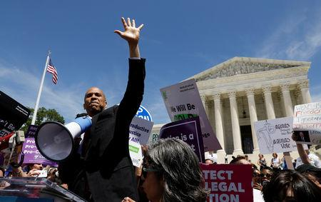 Democratic U.S. presidential candidate Sen. Cory Booker (D-NJ) waves to the crowd of protestors after addressing abortion rights activists during a rally outside the U.S. Supreme Court in Washington, U.S., May 21, 2019. REUTERS/Kevin Lamarque