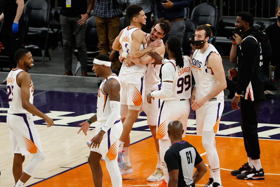 Devin Booker #1 of the Phoenix Suns celebrates with Dario Saric #20 after defeating the Portland Trail Blazers in the NBA game at Phoenix Suns Arena on May 13, 2021 in Phoenix, Arizona.  The Suns defeated the Trail Blazers 118-117. NOTE TO USER: User expressly acknowledges and agrees that, by downloading and or using this photograph, User is consenting to the terms and conditions of the Getty Images License Agreement. (Photo by Christian Petersen/Getty Images)