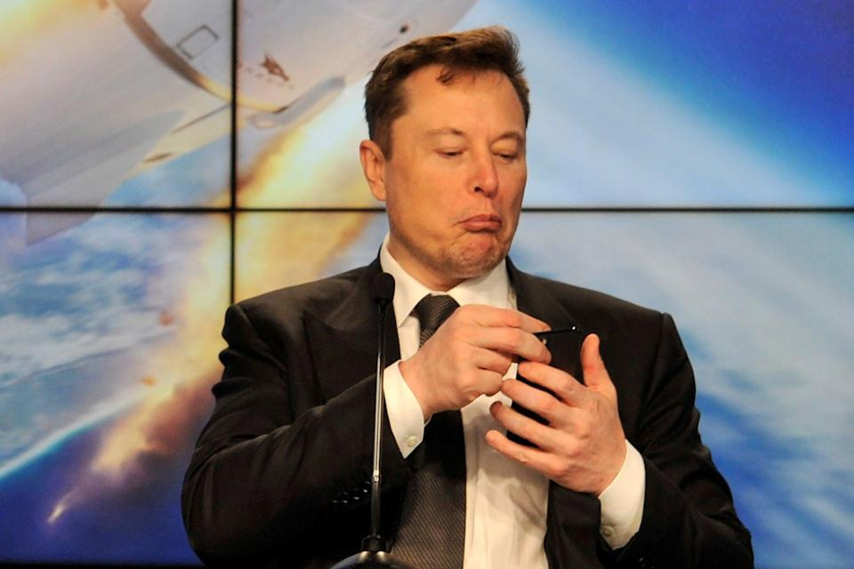 <p>File Image: SpaceX founder and chief engineer Elon Musk looks at his mobile phone during a post-launch news conference</p> (Reuters)