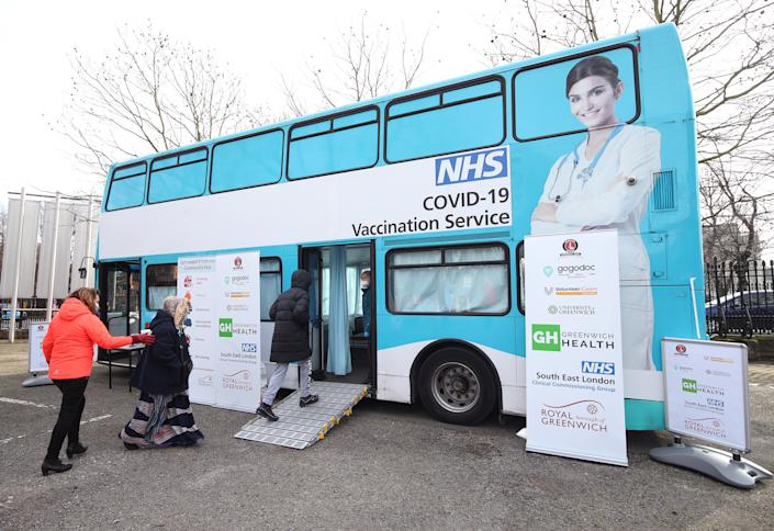 Members of the public receive their Covid-19 vaccinations on board a modified bus - donated by Gogodoc, an on demand GP booking service - in the car park of the University of Greenwich, London. Picture date: Saturday February 13, 2021.