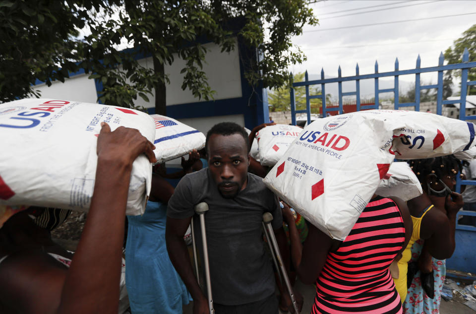 A man on crutches walks past people carrying corn flour sacks distributed by World Food Program outside at a police station in Port-au-Prince, Haiti, on Thursday, July 15, 2021. The country is in the midst of a heightened security situation after the July 7 assassination of President Jovenel Moise. (AP Photo/Fernando Llano)