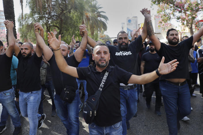 Supporters of the Shiite Hezbollah and Amal groups chant slogans against Judge Tarek Bitar, who is investigating last year's deadly seaport blast, during a protest in front of the Justice Palace, in Beirut, Lebanon, Thursday, Oct. 14, 2021. Lebanon's interior minister said at least five people have been killed in armed clashes in Beirut that erupted Thursday during protests against the lead investigator into last year's massive blast at the city's port. (AP Photo/Hussein Malla)
