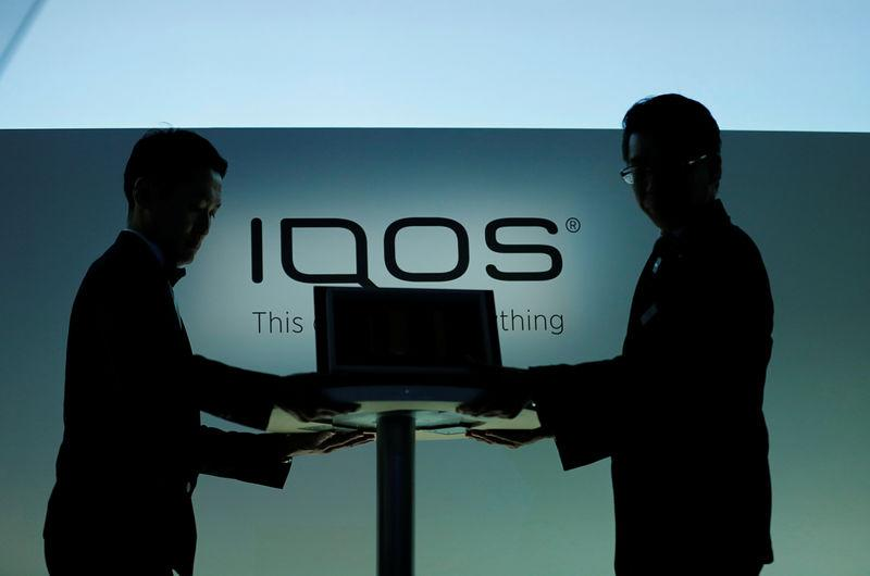 Staffs carry a table displaying Philip Morris new IQOS 3 devices during a news conference in Tokyo
