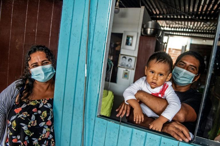 Nancy Sanchez, 48, poses with her husband Narciso and her grandchild at their home