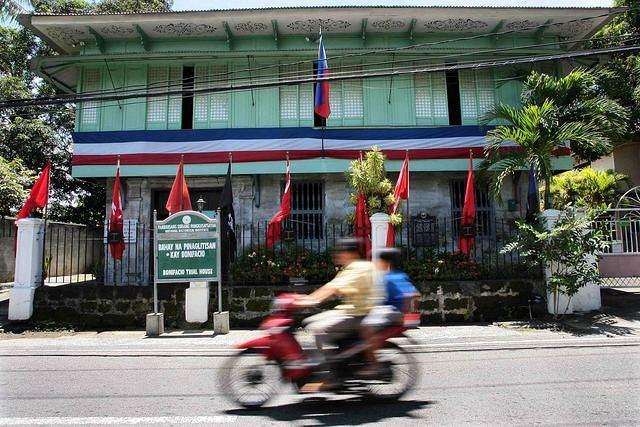 Filipinos on a motorcycle ride past the Bonifacio Trial House in Maragondon, Cavite province, located 60-kilometers south of Manila. Amidst the nationwide celebration of the country's 113th Independence Day, the Gat Andres Bonifacio Trial House, which is the only existing museum in honor of Bonifacio, was silent and did not hold any visitors. The trial house-museum will soon be removed as an agreement between the National Historical Institute and the lot owners will expire on 2014. Bonifacio, founder of the Katipunan and led Filipinos to revolt against Spanish colonizers, was tried with his brother Procopio by a court-martial in a house in Maragondon. Bonifacio and Procopio, was shot to death on May 10, 1897, on Mt. Nagpatong. (Mike Alquinto/NPPA Images)
